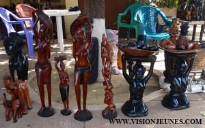 Loin de la capitale Conakry, Komara Ousmane est parmi ces artistes qui rêvent d'un lendemain meilleur pour l'artisanat guinéen. Spécialiste de l'art abstrait, cet artisan sculpte des œuvres qu'il expose dans la cour de l'hôtel Baté de Kankan. Entre passion et difficultés, Ousmane peine à vivre de son métier par faute d'assistance à l'artisanat et à la culture en général. De passage dans le nabaya, notre reporter est allé à sa rencontre. Lisez ! Bonjour, dites-nous comment êtes-vous arrivés dans l'art ? Bonjour, je suis né à Kankan mais j'ai quitté très tôt le pays pour aller en aventure. J'ai ensuite eu la chance de faire le management et j'ai essayé de contacter l'art guinéen depuis Abidjan. De retour en Guinée, je me suis spécialisé uniquement dans l'art pour faire la promotion de l'art guinéen à Kankan qui est la ville mère des artistes de Guinée parce que tous les grands artistes qui font l'art dans les autres pays d'Afrique viennent de Kankan ou ont comme maitre un kankanais qui les apprend à faire de l'art.  Que véhiculez-vous comme message dans vos œuvres d'art ? Je véhicule la souffrance de la femme africaine à travers la poupée de Kankan qui explique comment nos mamans souffrent. J'explique aussi les travaux champêtres à travers des statuts de cultivateurs. En général, dès que nous exprimons quelque chose, nous essayons de la faire pour pouvoir expliquer cette chose. Pour les colliers, on le fait à travers l'art abstrait pour dire aux gens qu'il faut l'union et l'amour pour qu'il y'ait la paix. Bref, nous essayons de faire comprendre que les fondements de toute chose restent l'amour et l'harmonie. Comment est-ce que votre activité d'artisan est perçue ici à Kankan ? Nous vivons une vie difficile ici à Kankan car ce n'est pas facile qu'on nous reçoit dans les hôtels parce qu'il n'ya pas de promotion de l'art ici alors que cette ville est réputée être une grande ville de l'art en Afrique.  Vous parvenez quand même à vendre vos œuvres à des acheteurs ? De temp